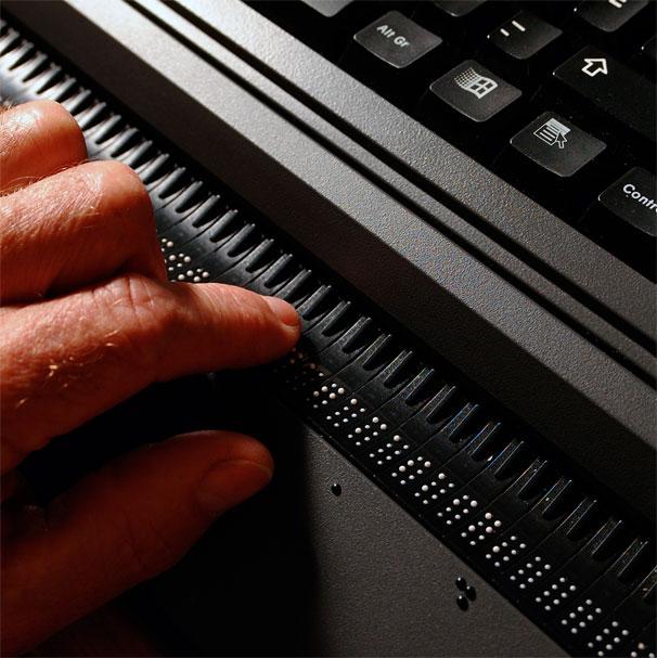 En hånd leser på en leselist. Punktene er hvite og stikker opp slik at de danner bokstaver. (Foto: Thomas Barstad Eckhoff)