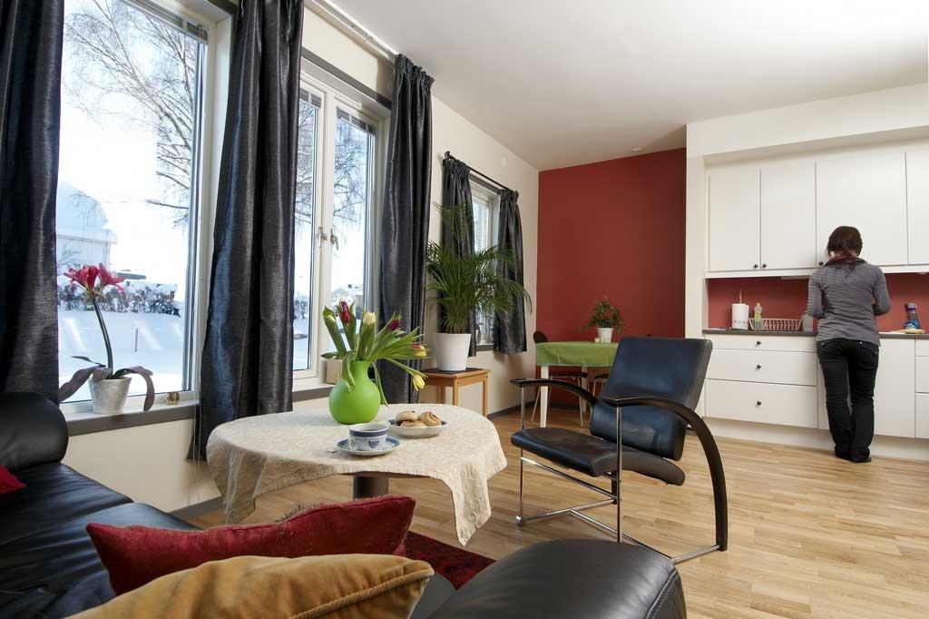 Bildet viser en åpen stue og kjøkkenløsning med god bruk av kontraster og jevn belysning