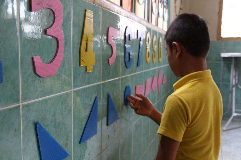 En gutt fra Laos kjenner på taktile bokstaver og figurer på en vegg.