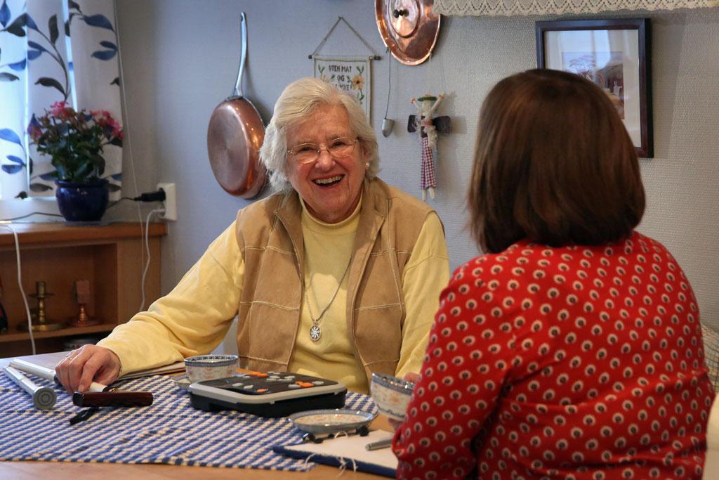 Laila Nygaard hjemme på kjøkkenet. På bordet foran henne ligger det et lite utvalg hjelpemidler som kan gjøre hverdagen hennes enklere.