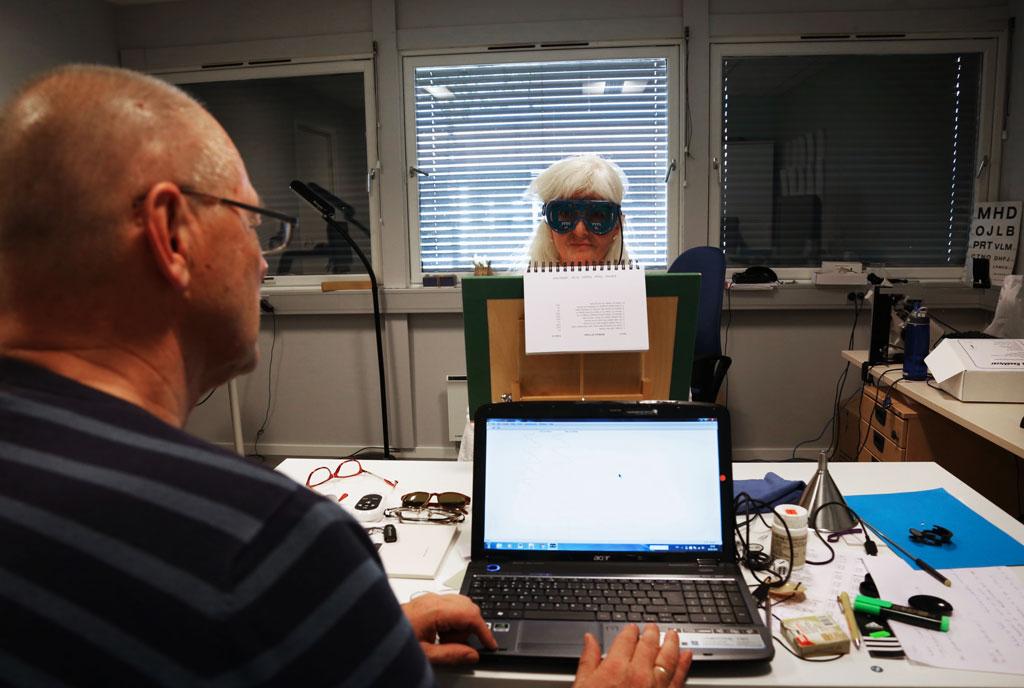 Arne ser på en dataskjerm, Mette sitter med en spesialbrille bak skjermen. Synet til Mette testes.