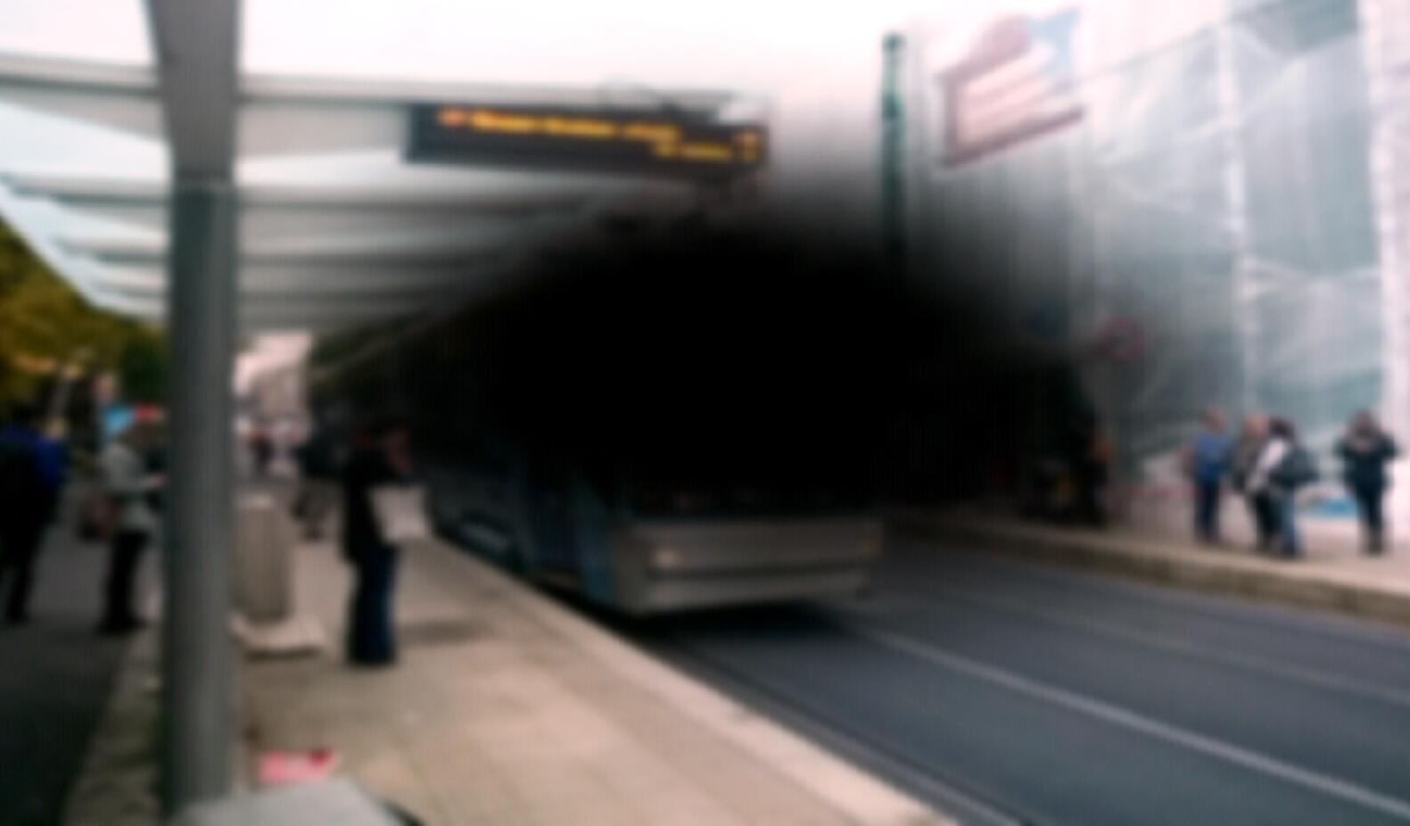 Slik kan en trafikksituasjon se ut for en person med AMD. Trikken på holdeplassen blir dekket av en mørk flekk i synsfeltet og omgivelsene er uskarpe.