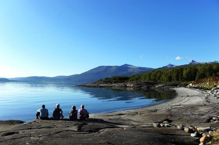 Evenes syn- og mestringssenter fire personer sitter ved vannkanten og ser utover fjorden
