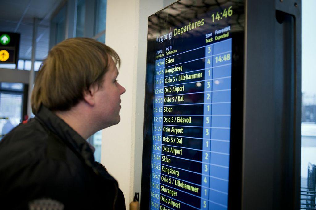 Bildet viser en person som ser på en digital informasjonstavle som er plassert i øyehøyde