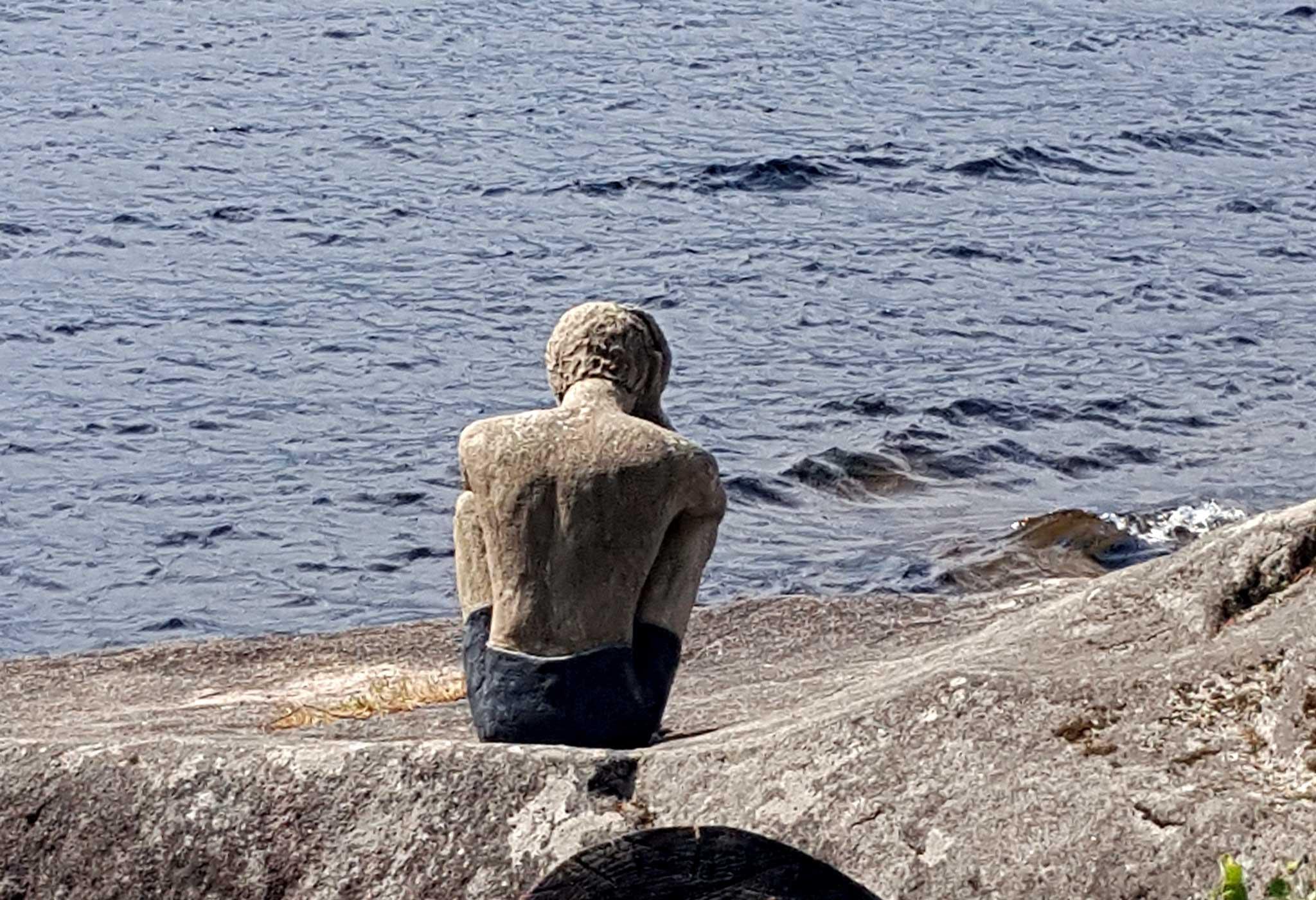 Bilde av statuen av mannen ved vannet. Bildet er tatt bakfra med Hurdalsjøen i bakgrunnen.