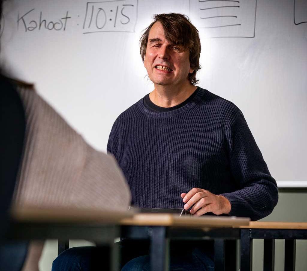 Rune Breck sitter ved kateteret foran en tavle. Foto: Per Ervland.