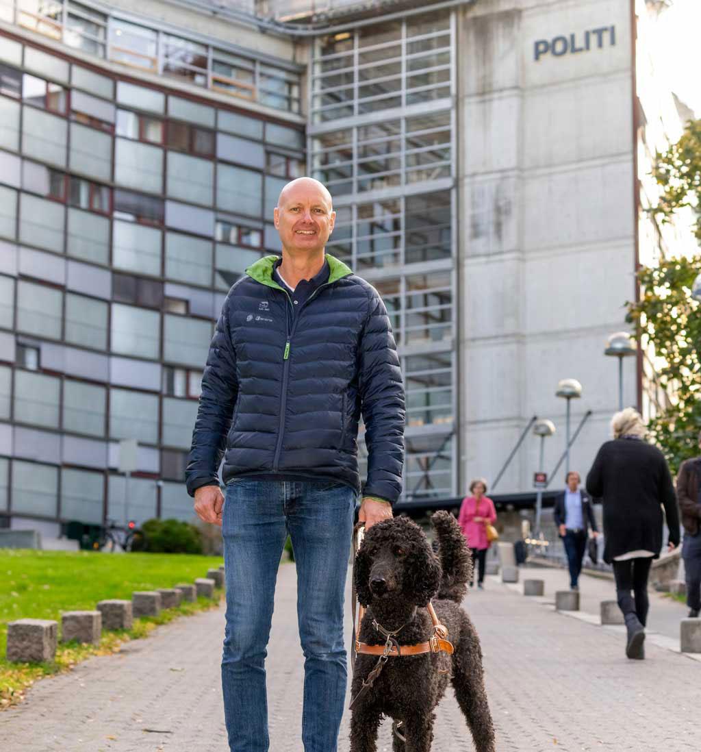 Håkon Gisholt med førerhund står foran politihuset i Oslo Foto: Per Ervland