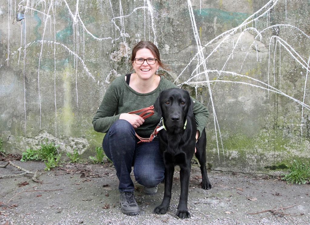 Anne-Birthe Dahle og Bilbo foran en murvegg