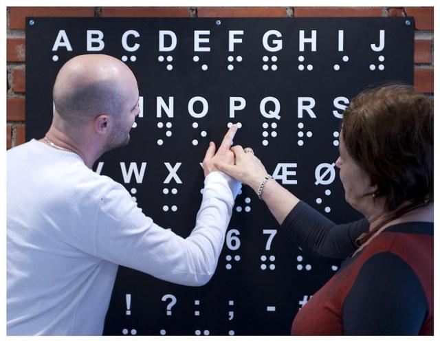 Eksempel på likemannsarbeidet i Blindeforbundet; en blind lærer en annen blind punktskrift