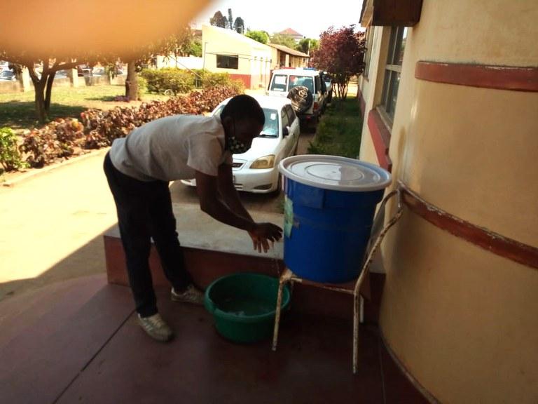 En pasient vasker hendene med klorvann før han kan gå inn på øyeklinikken.