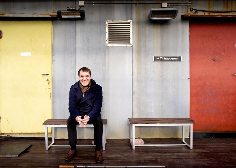 Per Inge sitter utendørs på en benk mellom to dører. Foto: Tom Egil Jensen.