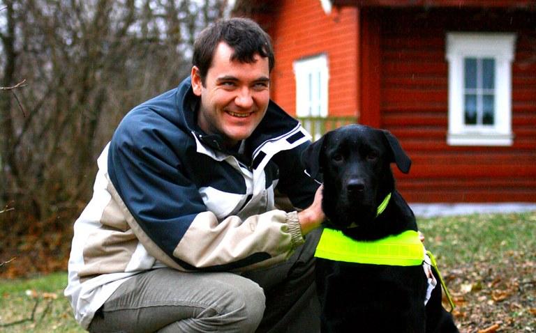 Per Inge sitter på hun på en gressplen sammen med det sorte labrador førerhunden hans Bosman.