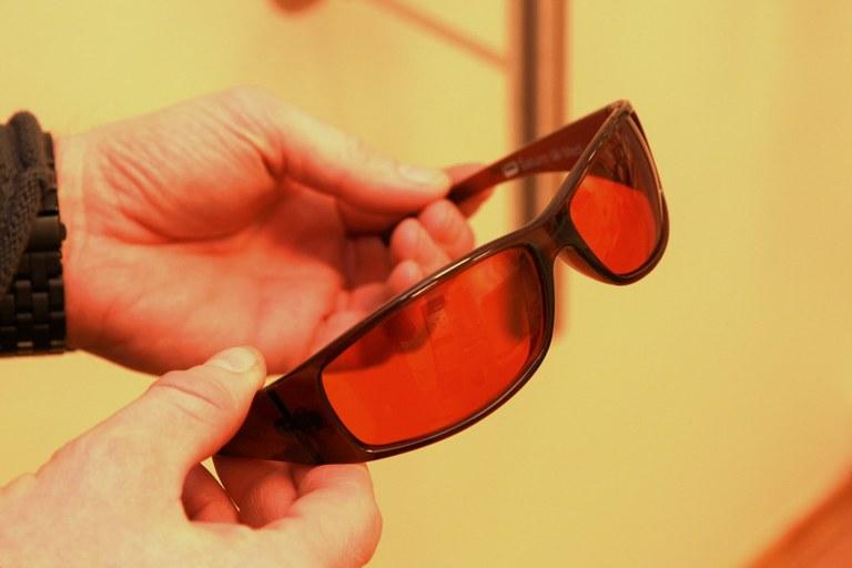Et par filterbriller med rødlig glass, holdes av en person.