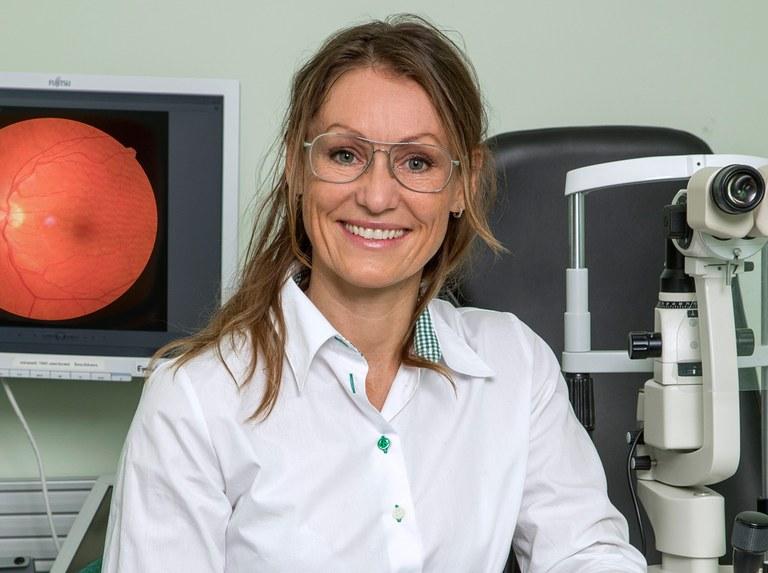 Optiker Trine Johnsen sitter ved en av maskinene som benyttes ved synsundersøkelser.