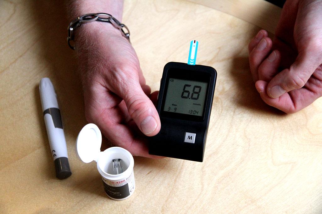 En person måler blodsukkeret sitt og hører apparatet lese opp verdien som også er synlig på skjermen.