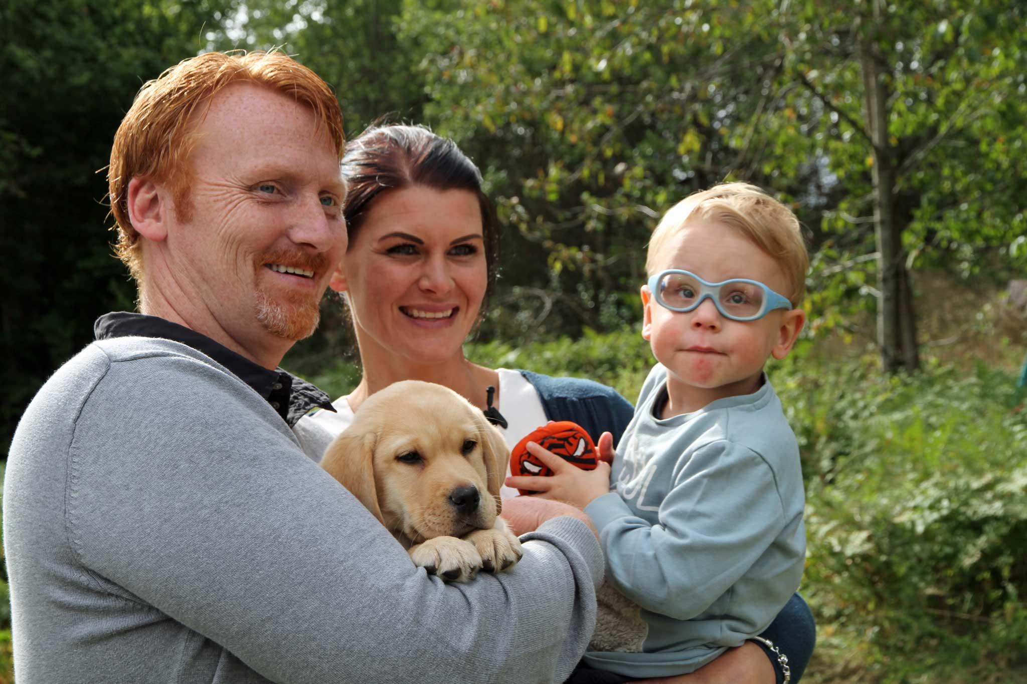 En familie på to voksne og et barn, holder en lys labrador retriever.